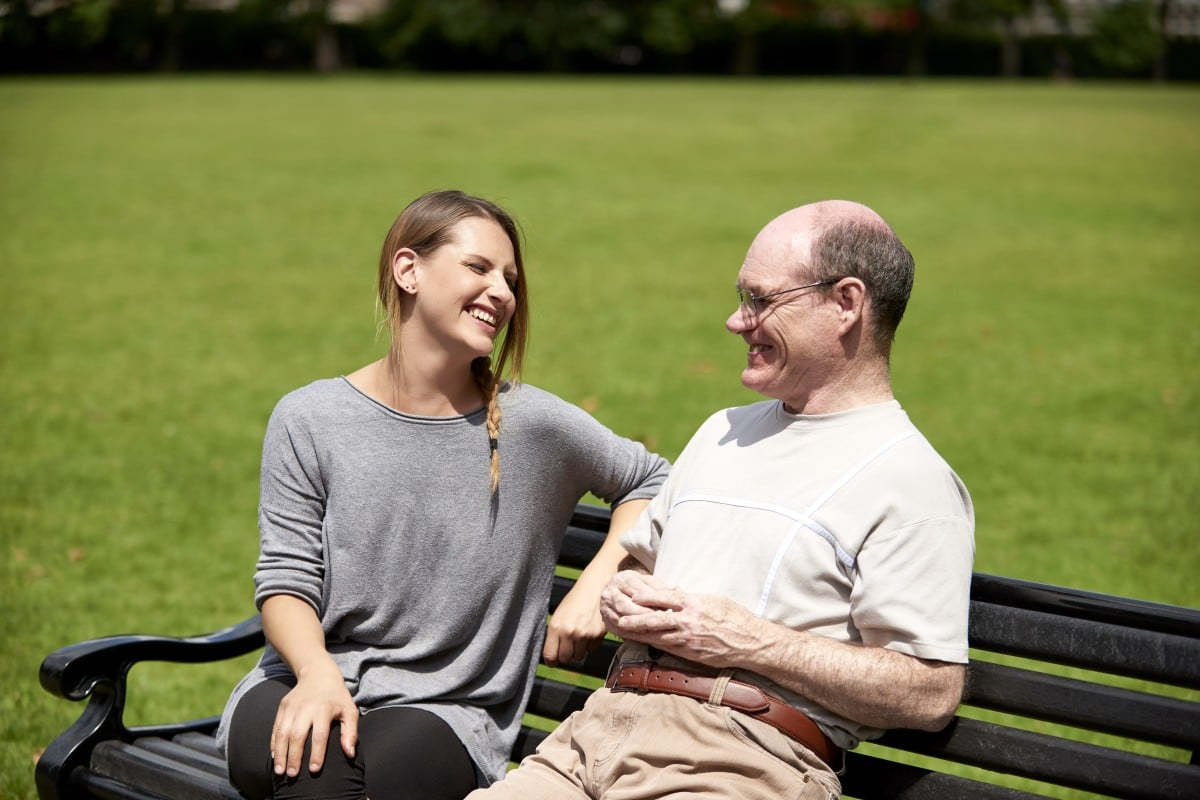 Jess, Support worker sat with Rob, her client on a bench