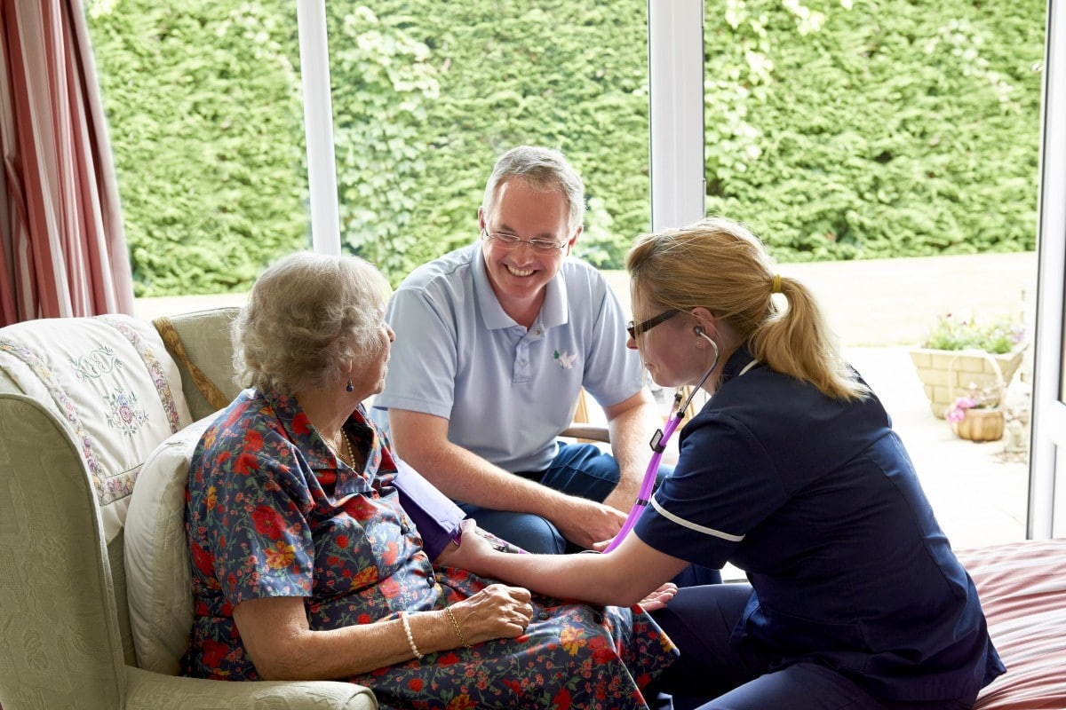 Care worker Philip sitting with Jules his client whilst she has her blood pressure taken by a nurse